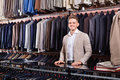 Man seller displaying diverse suits in men's cloths store Royalty Free Stock Photo