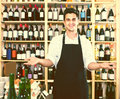 Man seller wearing uniform standing in shop with wine