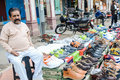 A man selling shoes by displaying his collection on road Stock Image