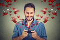 Man sending love sms message on mobile phone with hearts flying away portrait happy text red from screen isolated grey wall Royalty Free Stock Photography