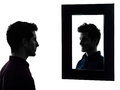 Man serious in front of his mirror silhouette shadow white background Stock Images