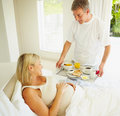 Man serving breakfast to his pregnant wife on bed Stock Image