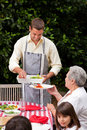 Man serving his mother at the table Stock Images