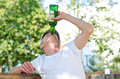 Man with a severe drinking problem upending bottle of spirits gulping down alcohol as he sits outdoors under leafy green trees Stock Photography