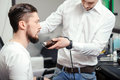 Man shaves his beard with a hair clipper perfectly styled young bearded men getting shaved and comb in barber shop or salon Stock Images