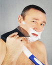 Man is shaving with an axe Royalty Free Stock Image