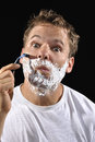 Man shaving handsome caucasian with messy bed head hair makes funny face while his cheek on black background Royalty Free Stock Photography