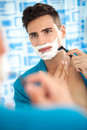 Man shaving his beard young with a razor in bathroom Royalty Free Stock Photography