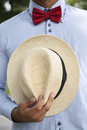 Man in shirt, red bow-tie holding white wicker hat Royalty Free Stock Photo