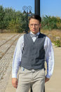 Man in shirt and vest with bow tie and glasses standing leaning against a lamppost the old vintage park or town looking at Stock Photography