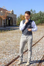 Man in shirt and vest with bow tie and glasses standing in line lines of railway the old vintage park or town looking aside Royalty Free Stock Photo