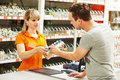 Man shopping at hardware supermarket young women help purchaser choosing plumber equipment in mall Stock Photo