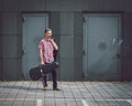 Man in short sleeve shirt holding guitar case the street Stock Photography