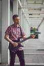 Man in short sleeve shirt playing electric guitar the street Royalty Free Stock Image