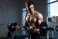 stock image of  Man in shorts with a barbell trains in the gym close-up