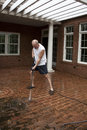 Man shorts powerwashing dirt brick patio Royalty Free Stock Photos