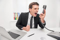 Man shouting young is by phone Royalty Free Stock Photography