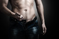 Man showing his muscular body low key stripper unzips jeans and belt Stock Photos