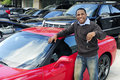 Man showing key of new red sports car Royalty Free Stock Photo