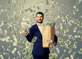Man showing money excited young businessman standing under dollar s rain holding big paper bag and Royalty Free Stock Image