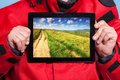 Man showing mountains on tablet travel closeup of male hands holding ipad with photo of traveler screen touchpad dreaming about Royalty Free Stock Images