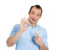 Man showing ok sign closeup portrait of sarcastic smiling young funny looking guy pointing with index finger at it isolated on Stock Photos
