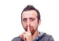Man showing silent sign closeup portrait of placing finger on lips as if to say shhhhh be quiet silence isolated on white Royalty Free Stock Photo