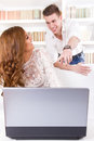 Man showing something to his pretty wife on a screen in their li casual young men living room Royalty Free Stock Images