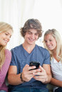 Man showing the two girls whats on his phone Stock Photo