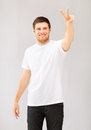 Man showing victory or peace sign young in white blank t shirt Stock Photo