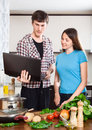 Man shows the new recipe to girl at kitchen table Stock Photography