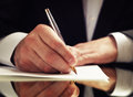 Man signing a document or writing correspondence with close up view of his hand with the pen and sheet of notepaper on desk Royalty Free Stock Photography