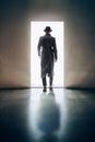 Man silhouette walking away in the light of opening door in dark