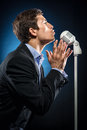 Man singing in elegant black jacket and blue shirt Stock Photos
