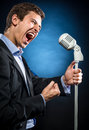 Man singing in elegant black jacket and blue shirt Royalty Free Stock Photo