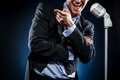 Man singing in elegant black jacket and blue shirt Royalty Free Stock Photography