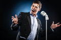 Man singing in elegant black jacket and blue shirt Stock Photo