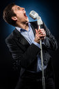 Man singing in elegant black jacket and blue shirt Stock Photography