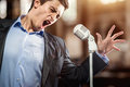 Man singing in elegant black jacket and blue shirt Royalty Free Stock Photos