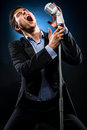 Man singing in elegant black jacket and blue shirt Stock Images
