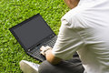 Man siting on the grass using laptop Stock Photography