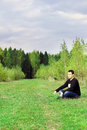Man sits on grass on edge of forest at autumn dull day and thinks Royalty Free Stock Photos