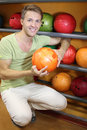 Man sits near shelves with balls and holds ball Royalty Free Stock Image