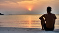 Man sits at sunrise on Koh Pangan