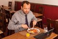 Man sitting alone in restaurant with laptop Royalty Free Stock Photo