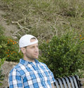 Man sitting with a backwards hat white in plaid shirt on bench in park looking out Stock Photo