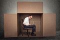 Man sitting in a box working on laptop Royalty Free Stock Photo
