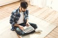 Man sitting on carpet and typing on laptop Royalty Free Stock Photo