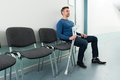 Man sitting on chair with crutches Royalty Free Stock Photo