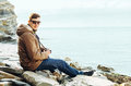 Man sitting on coastline with photo camera Royalty Free Stock Photo